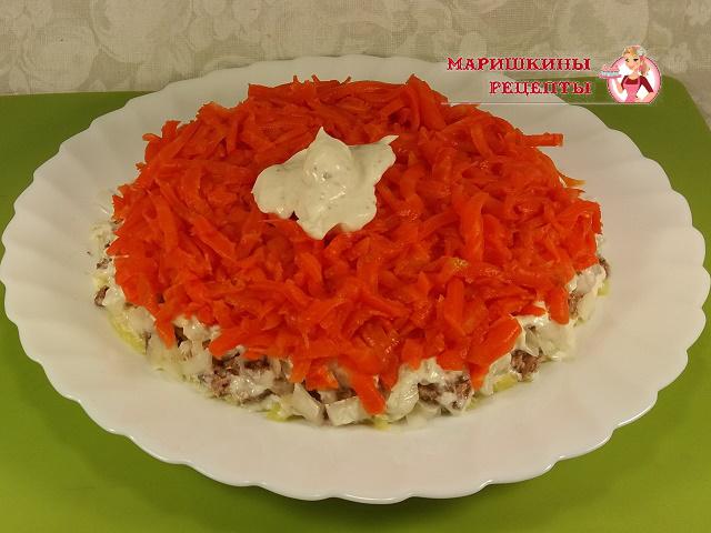 Натертую морковь выкладываем поверх лука и смазываем майонезом